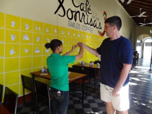 "Since last year, Antonio has opened a cafe that employs deaf and mute people. To order, you must use sign language. In this picture, our professor, Peter Roberts, is signing his name out to one of the waitresses. Unbelievably cool stuff. The name of the place, ""Cafe de Las Sonrisas"" means Cafe of the Smiles."